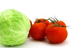 在分支的红色蕃茄和在白色背景的年轻圆白菜新芽 库存图片