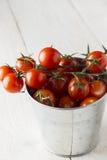 在分支的西红柿在金属在木背景用桶提 库存照片