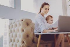 在分散她的新生儿介入的兴旺的销售经理感觉 库存照片