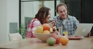 在分析某事从膝上型计算机的现代厨房成熟夫妇,当采取他们的健康早餐射击了时 股票录像
