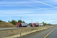 在分道公路的大和小半船具卡车护卫舰赛跑有另一交通的 免版税库存图片