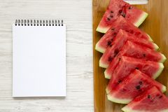 在切口竹委员会的切的新鲜的成熟西瓜有在白色木背景,顶视图的空白的笔记本的 库存照片