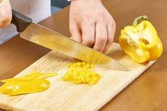 在切在专业厨房的手上的特写镜头黄色胡椒 库存图片