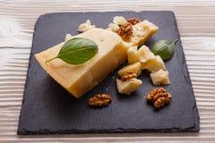 在切委员会的板岩石头的芬芳巴马干酪 图库摄影