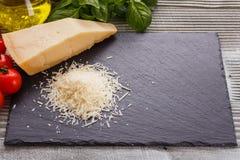 在切委员会的板岩石头的芬芳被磨碎的巴马干酪 库存图片