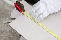 在切开前的铺磁砖工测量的瓦片 库存照片