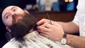 在切开胡子与电整理者剃刀由理发师手和梳的焦点 人正面图有卷曲黑暗的胡子的 影视素材