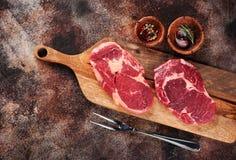 在切板、大蒜、迷迭香和胡椒的两块未加工的ribeye牛排 库存图片