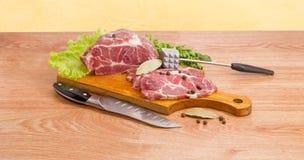 在切板、肉软化剂和厨刀的猪肉脖子 图库摄影