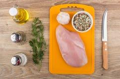 在切板、香料、大蒜和厨房knif的鸡内圆角 库存图片