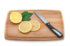 在切板上是一些个切片新鲜的柠檬和刀子 库存照片