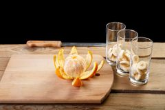 在切板上是被剥皮的桔子,在与香蕉片断的玻璃旁边,为水果鸡尾酒准备 图库摄影