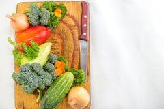 在切板和刀子的新鲜蔬菜 与copyspace的食物简单的背景 免版税库存图片