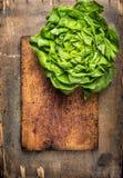 在切板和木桌,食物背景的新鲜的莴苣 免版税库存照片