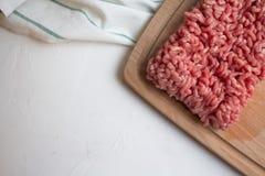 在切板和洗碗布的顶视图未加工的肉末在一张白色桌上 免版税库存照片