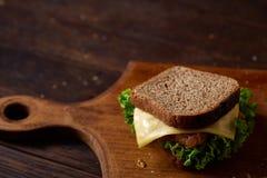 在切板在黑暗的木背景,特写镜头的鲜美和新鲜的三明治 免版税库存照片