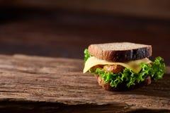 在切板在黑暗的木背景,特写镜头的鲜美和新鲜的三明治 免版税库存图片