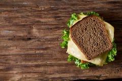 在切板在黑暗的木背景,特写镜头的鲜美和新鲜的三明治 免版税图库摄影