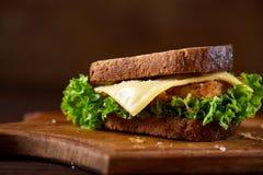 在切板在黑暗的木背景,特写镜头的鲜美和新鲜的三明治 图库摄影