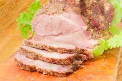 在切板特写镜头的部分被切的被烘烤的猪肉脖子 免版税库存照片