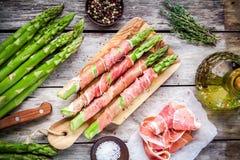 在切板的帕尔马火腿包裹的新鲜的有机芦笋 库存照片