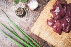 在切板的新鲜的鸡肝,红洋葱,在棕色木背景的葱用疏散米 免版税图库摄影