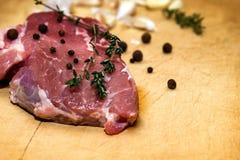 在切板的未加工的使有大理石花纹的牛肉 在黑色背景 图库摄影