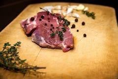 在切板的未加工的使有大理石花纹的牛肉 在黑色背景 库存图片