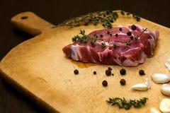 在切板的未加工的使有大理石花纹的牛肉 在黑色背景 免版税库存照片