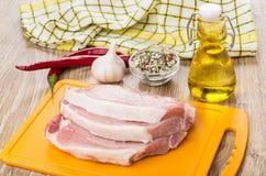 在切板的未加工的猪肉炸肉排,香料,大蒜,胡椒,油 图库摄影