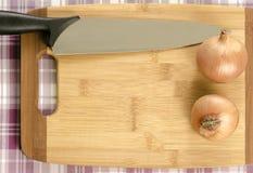 在切板的葱和刀子。 免版税库存图片