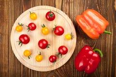 在切板的西红柿和在木后面的胡椒响铃 库存照片