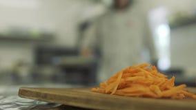 在切板,工作在被弄脏的背景的厨师的Cuuted红萝卜 股票录像