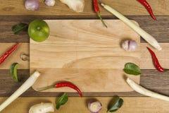 在切板,辣椒,香茅,柠檬叶子的新鲜蔬菜在木背景设置了 库存照片