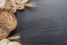 在切片、麦子和一把刀子上添面包在黑石书桌上 免版税库存照片