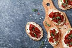 在切片上添面包用乳脂干酪和各式各样的蕃茄在木台式视图 可口快餐和开胃菜 免版税图库摄影