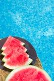 在切片楔子的成熟水多的无核的西瓜裁减在藤条表上的板材由游泳池 阳光 假期 免版税库存照片
