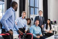 在创造性的办公室、非裔美国人的商人举行自行车,队会议和沟通的商人小组 库存图片