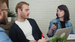 在创造性的办公室时合作与膝上型计算机一起使用,当坐在书桌 股票录像
