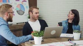 在创造性的办公室时合作与膝上型计算机一起使用,当坐在书桌 股票视频