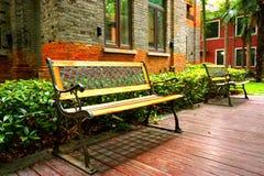 在别墅房子旁边的两个长木凳 库存照片