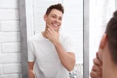 在刮的英俊的人在镜子附近以后 库存图片
