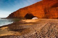 在到达在海的Legzira剧烈的巨大的红色自然石曲拱的日落 大西洋,摩洛哥, Sidi Ifni 免版税库存照片