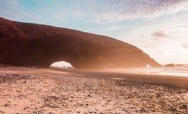 在到达在海的Legzira剧烈的巨大的红色自然石曲拱的日落 大西洋,摩洛哥, Sidi Ifni 库存图片
