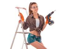 在制服和玻璃的年轻深色的妇女建造者做整修与操练摆在她的手看和  库存照片