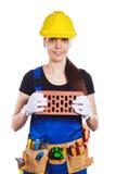 在制服的妇女建造者拿着一块砖 免版税库存照片