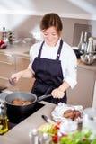在制服的微笑的女性kitchener在厨房里站立在餐馆 库存图片