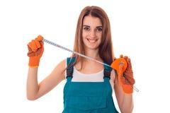 在制服的愉快的年轻深色的妇女建造者有手套的做整修和看照相机和微笑 库存图片