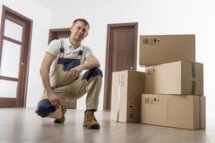 在制服的搬家工人有纸板箱的在房子里公寓屋子  拆迁为概念服务 库存照片