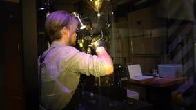 在制服的白肤金发的男性barista油煎在一个特别机器的咖啡豆 影视素材
